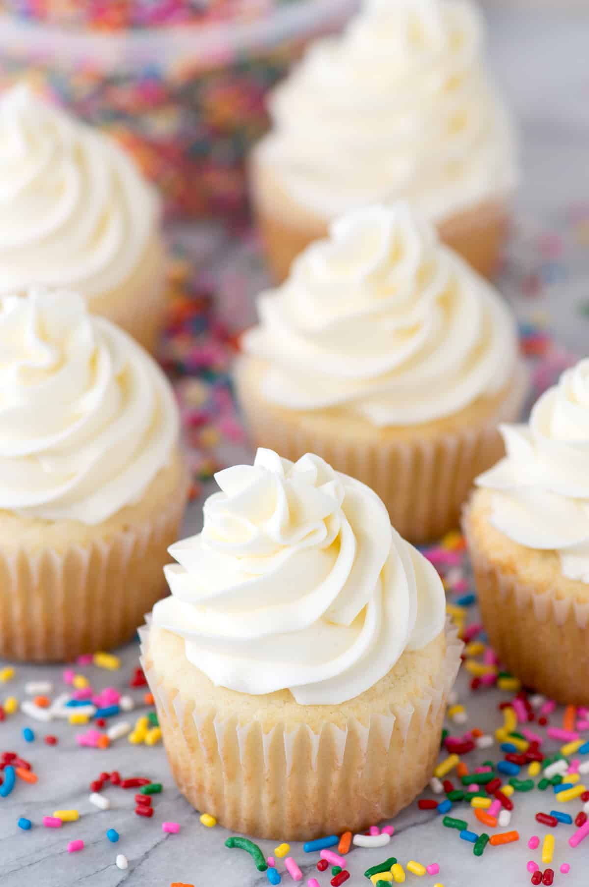 vanilla cupcakes with white frosting on marble background with sprinkles on the marble