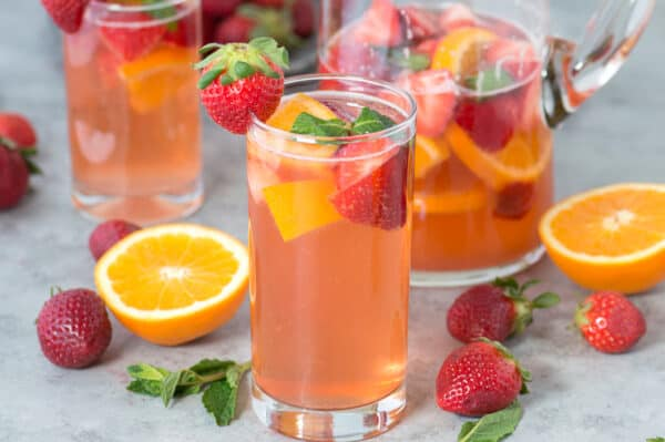 strawberry sangria in clear glass with strawberries, oranges and mint as garnish