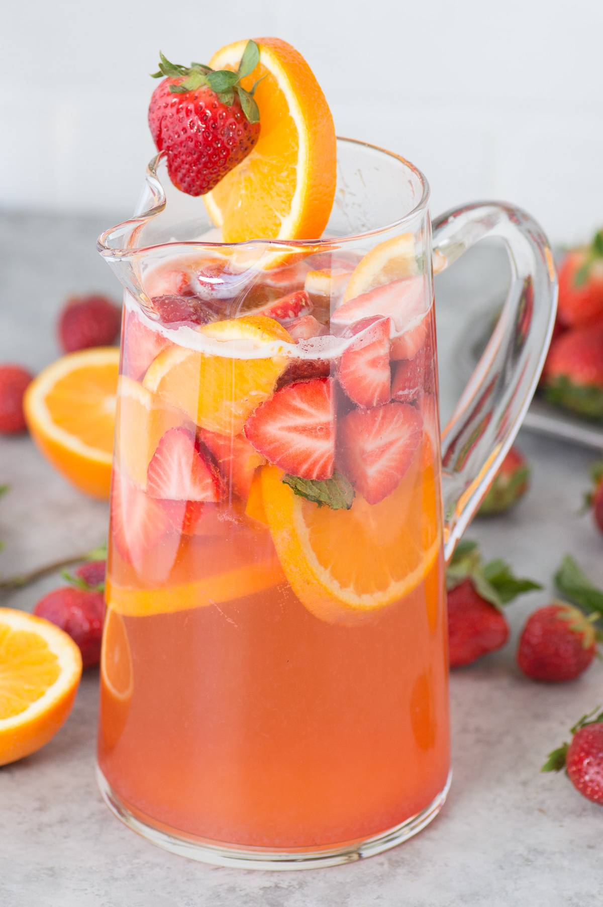 Glass pitcher of delicious Strawberry Sangria with sliced oranges and fresh strawberries.
