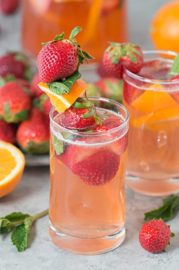 Two glasses of Strawberry Sangrias garnished with strawberries and sliced oranges.