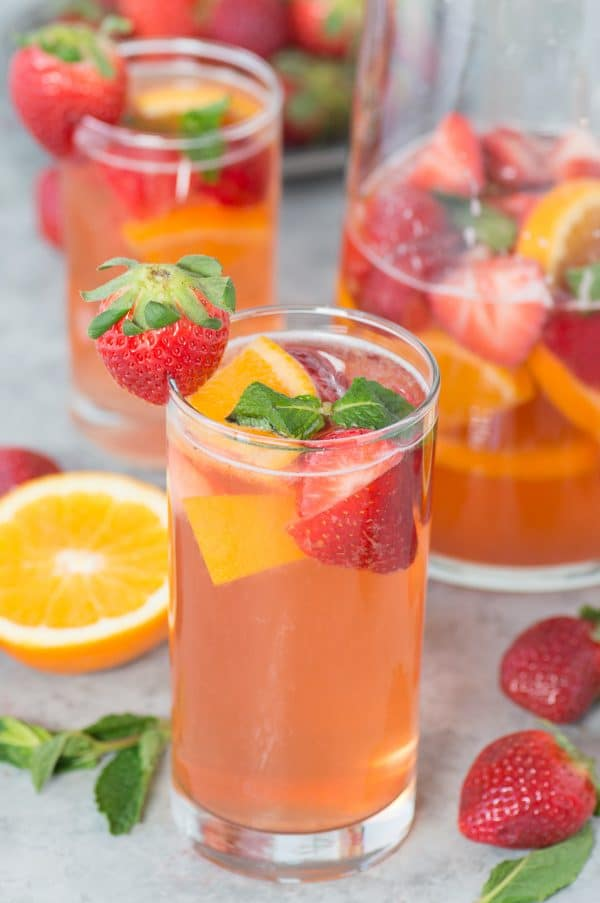 Three homemade Strawberry Sangrias garnished with fresh oranges and strawberries.