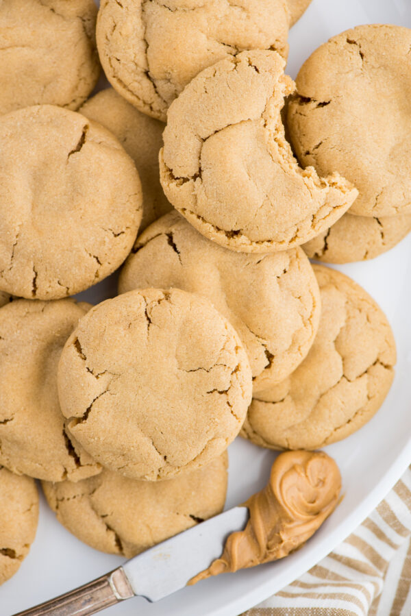 peanut butter cookies on white plate with butter knife with peanut butter on white background