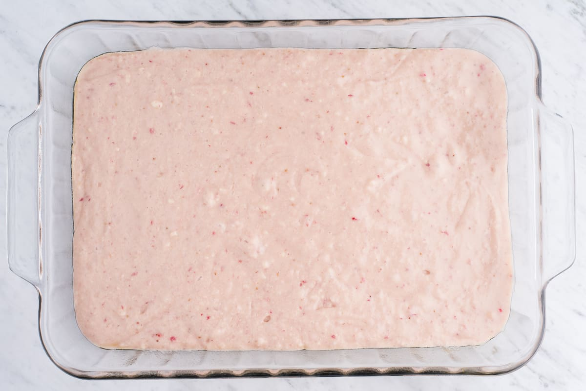 strawberry cake batter in glass pan on white background