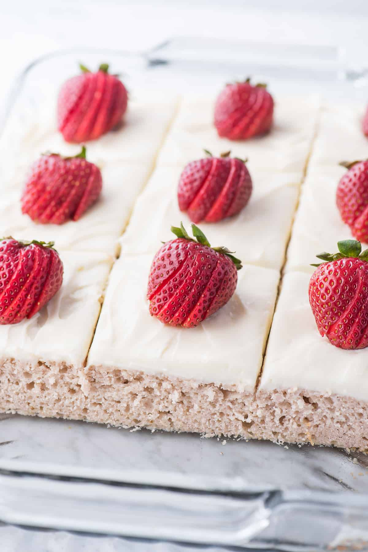 strawberry cake in glass pan with white frosting and a strawberry on each piece