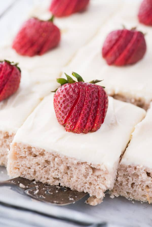 strawberry cake with white frosting and strawberry on top on metal spatula