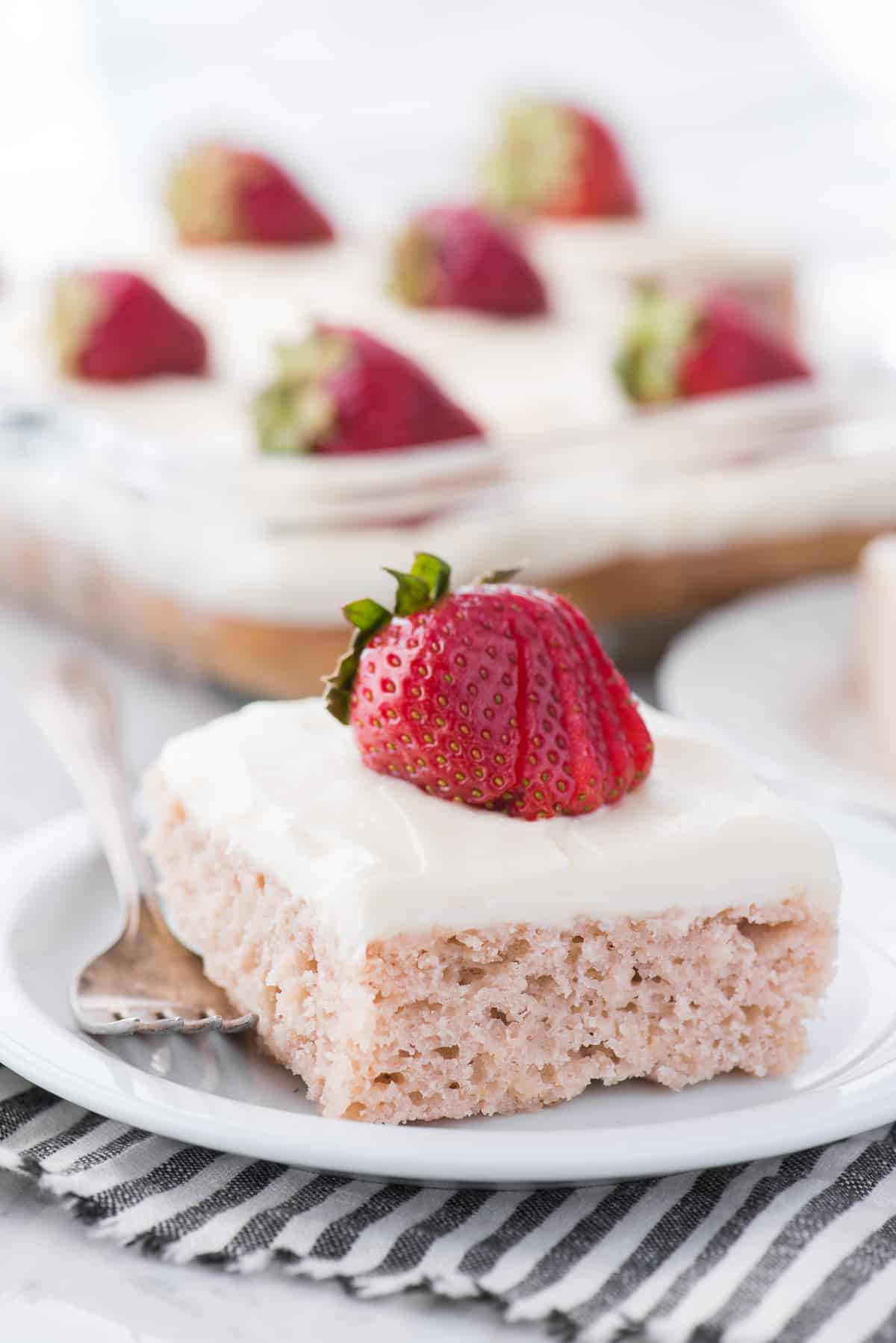 strawberry cake with white frosting and strawberry on top on white plate