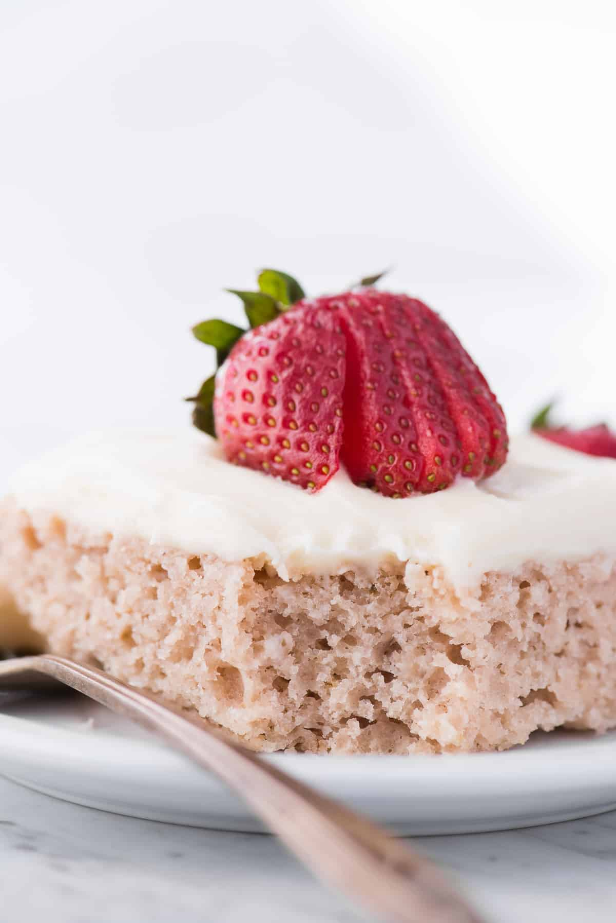 strawberry cake with cream cheese frosting on white plate with bite removed