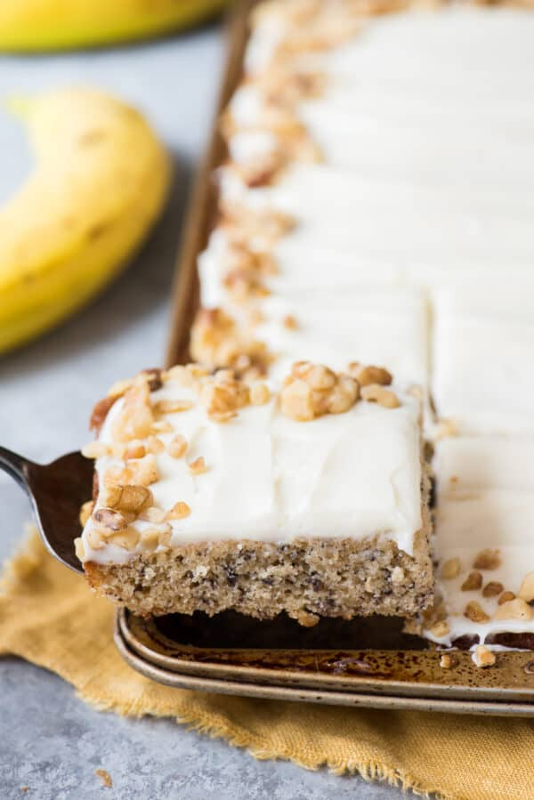 spatula holding slice of banana bar with cream cheese frosting