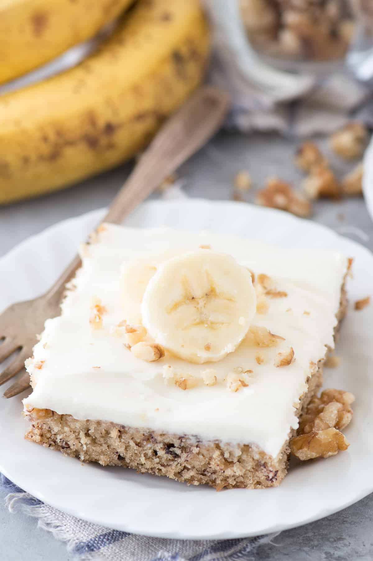 banana bar with cream cheese frosting and banana slice on white plate