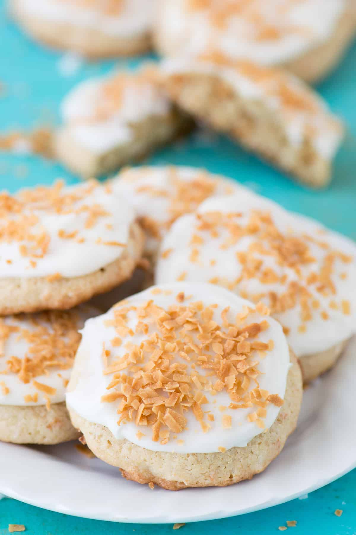 coconut cookies with white frosting on white plate on teal background