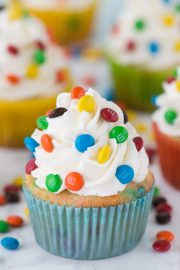 Loaded M&M cupcakes! Moist vanilla cupcakes with mini M&Ms in the batter, topped with vanilla buttercream and more mini M&Ms!