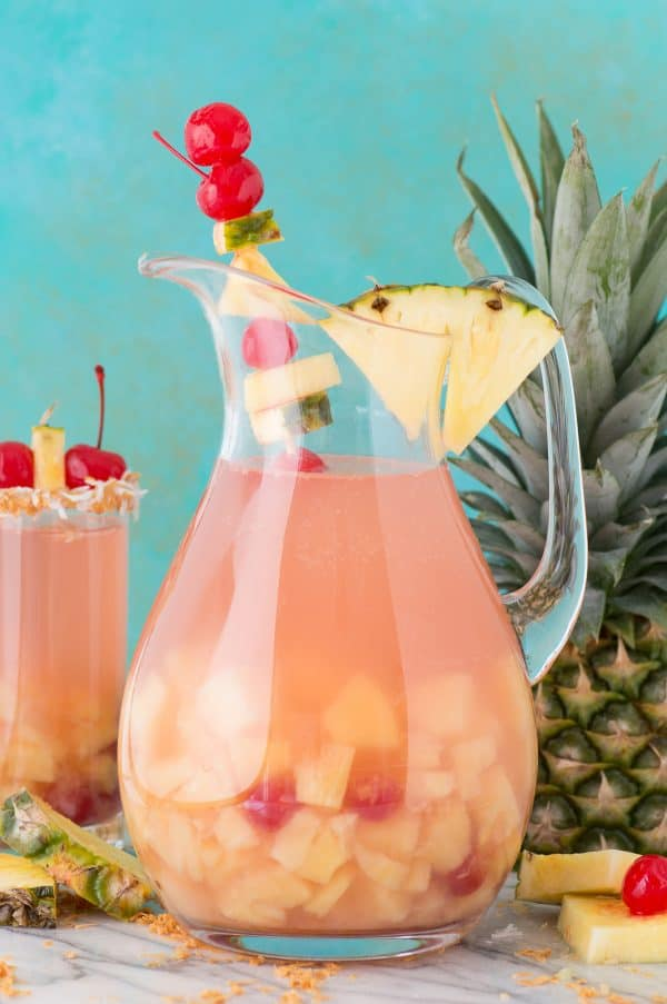 pina colada sangria in a glass pitcher with pineapple and cherry for garish