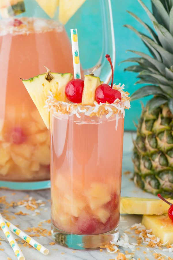 pina colada sangria in a glass cup with pineapple and cherry for garish