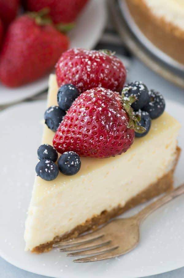 slice of classic plain cheesecake with fruit on top on white plate