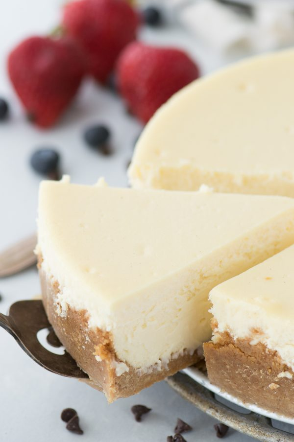 slice of classic plain cheesecake being removed from whole cheesecake