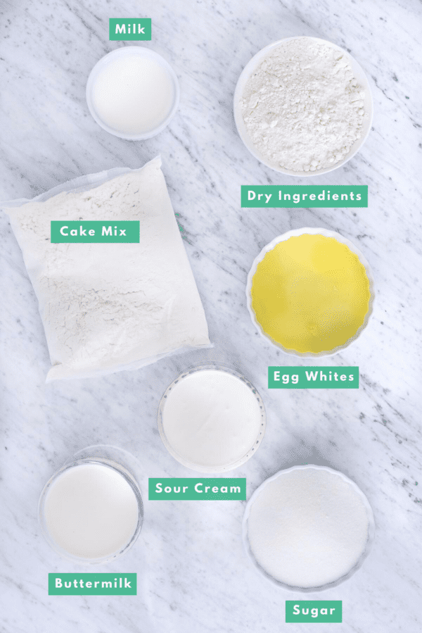 ingredients to make white cake mix from box mix on marble background with text overlay