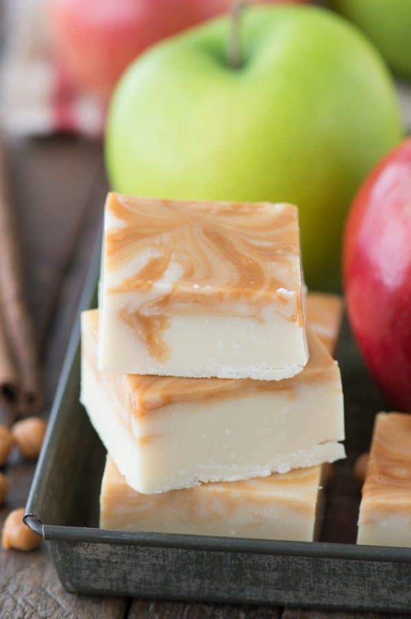 caramel apple fudge in a stack in metal tray with apples in background