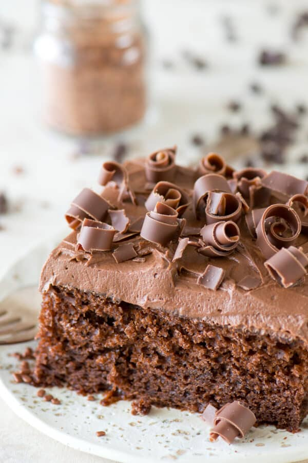 slice of chocolate cake with chocolate frosting and chocolate curls on white plate
