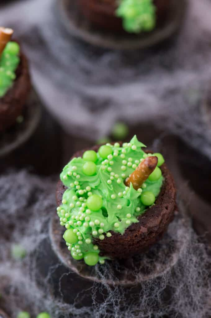 mini brownie bites filled with green frosting and green sprinkles to look like a bubbling witch's cauldron