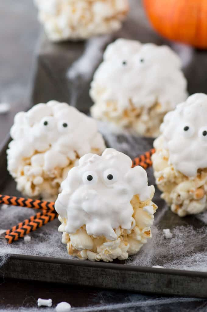 popcorn balls covered in white chocolate with candy eye balls to look like ghosts