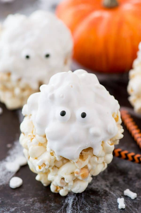 popcorn balls that look like ghosts - covered in white chocolate with candy eye balls