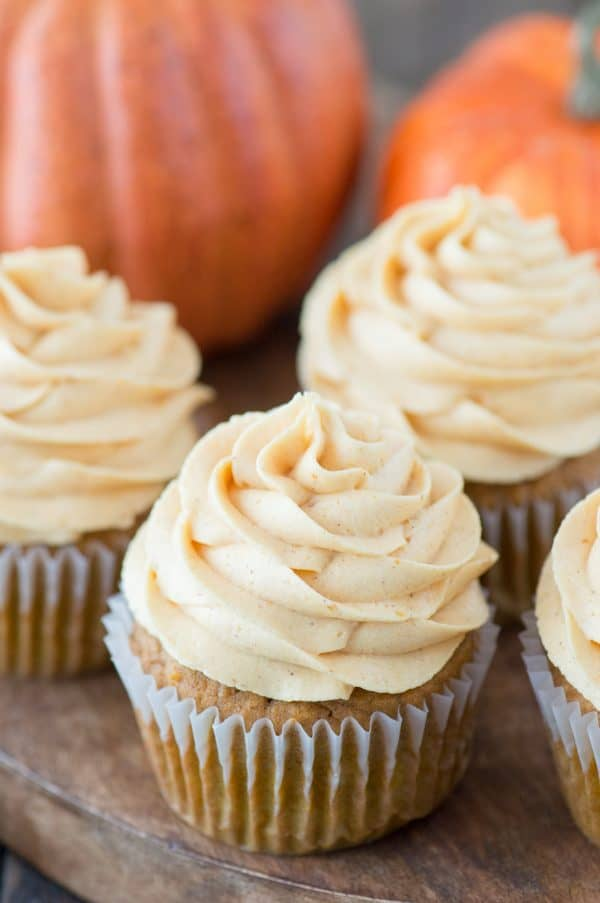 pumpkin cupcakes with pumpkin frosting on wooden tray