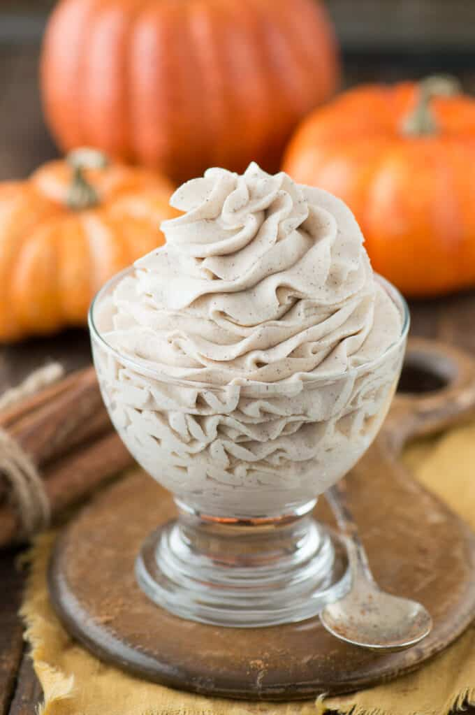 pumpkin whipped cream piped into clear bowl on wooden background