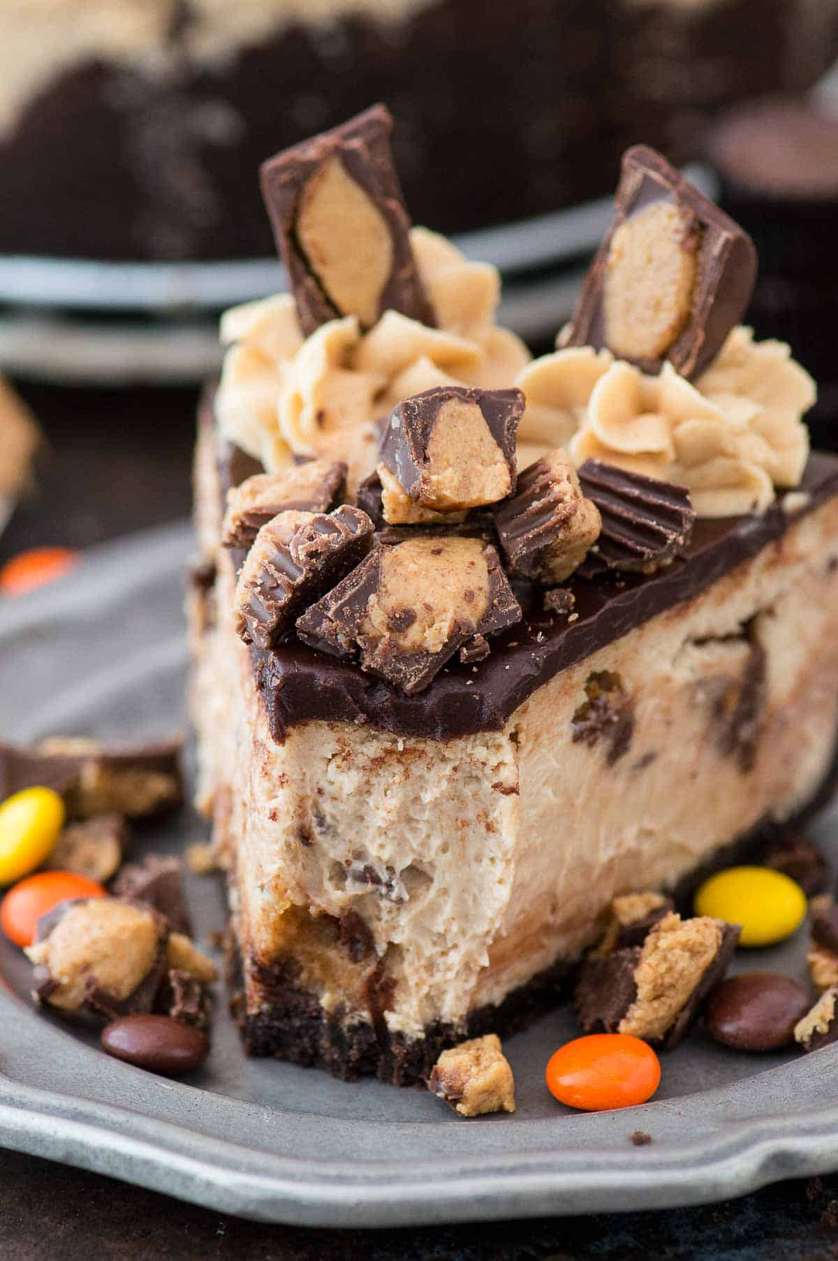 slice of reese's cheesecake with chocolate ganache and more reese's cup on metal plate