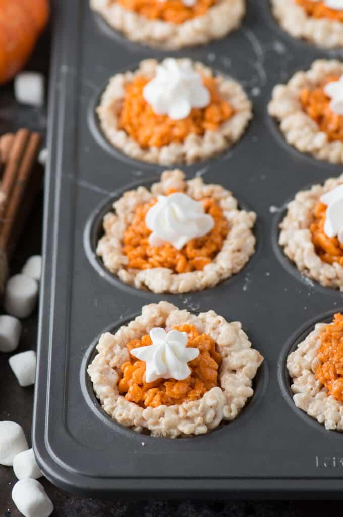 rice krispie treats that look like mini pumpkin pies in metal muffin pan