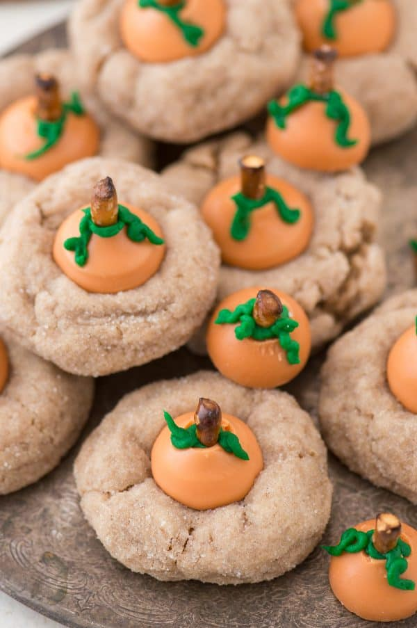 These are the most adorable fall cookies - pumpkin blossom cookies! A spice cookie with pumpkin spice hershey's kisses turned into PUMPKINS!