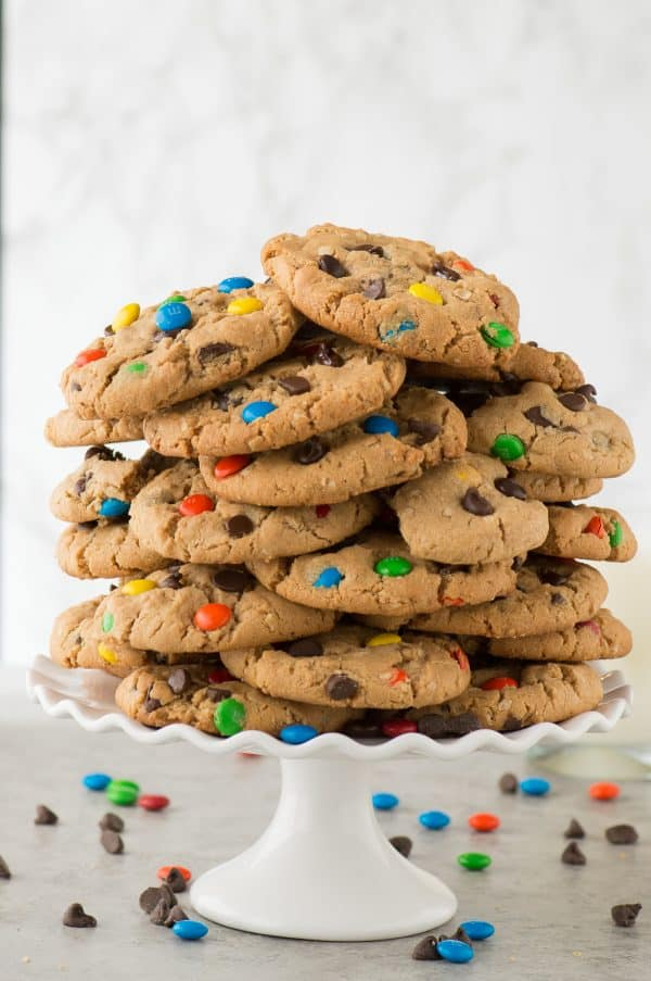 monster cookies in a giant stack on a white cake stand