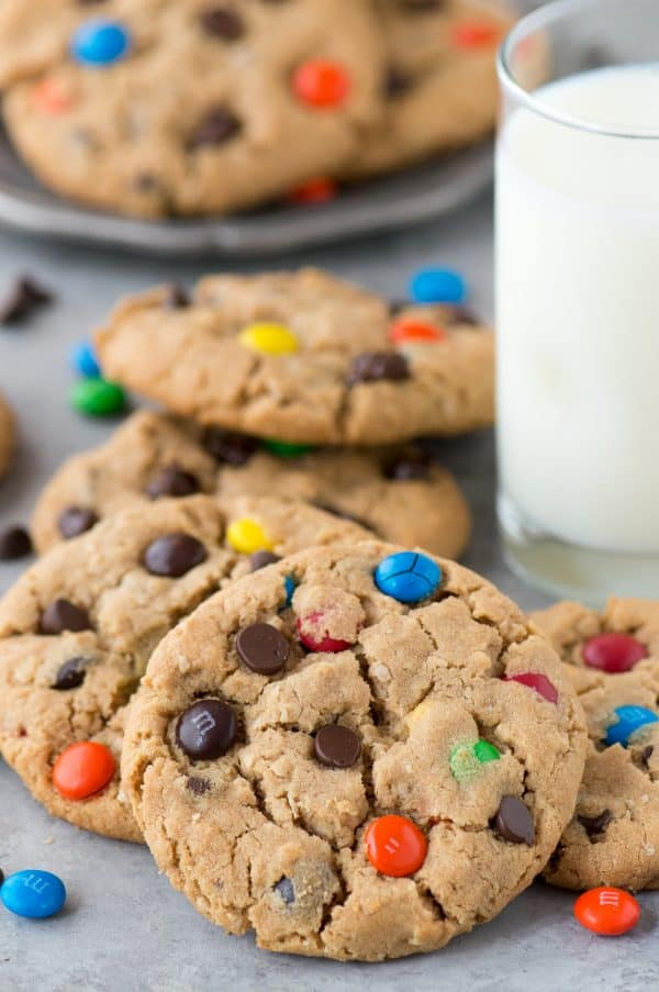 monster cookies with m&ms and chocolate chips with glass of milk in the background