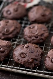 Homemade healthier dark chocolate coconut oil cookies on a cooling rack.