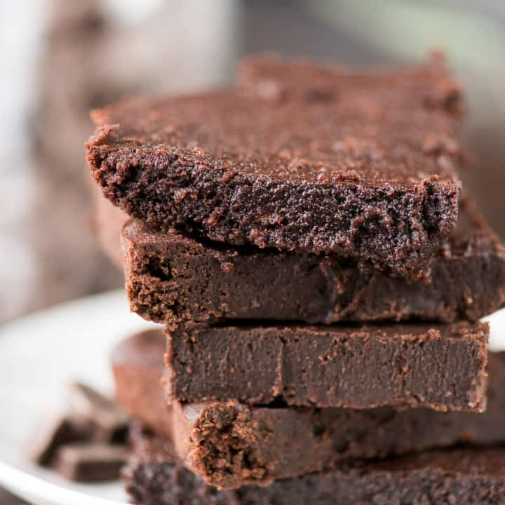 Five homemade healthier fudgy brownies on a white serving plate.