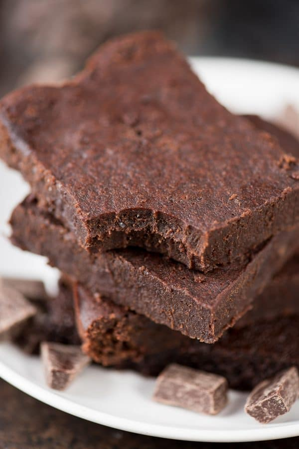 Three healthy fudgy brownies surrounded by small chocolate pieces on a white serving plate.