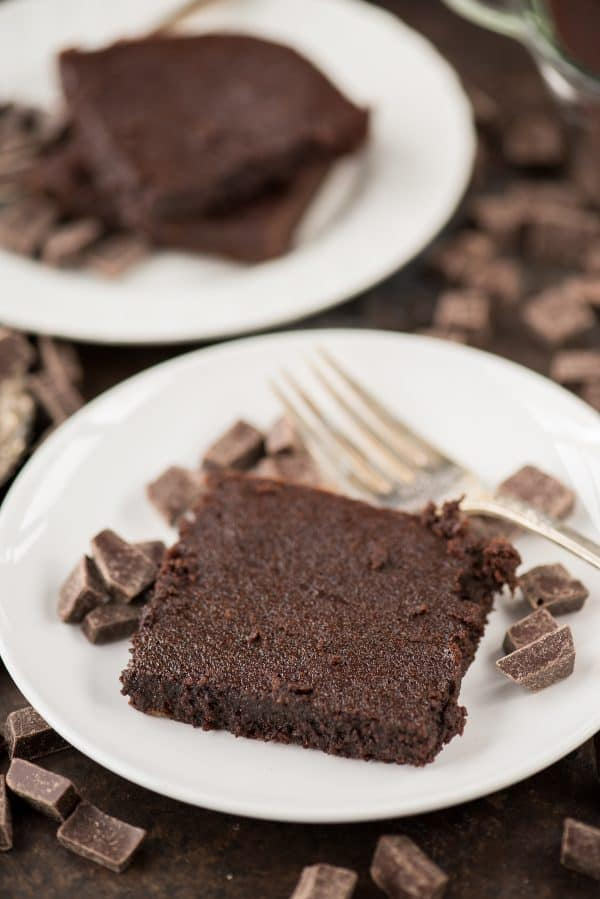 One healthier fudgy brownie with small chocolate and a silver fork on a white plate.