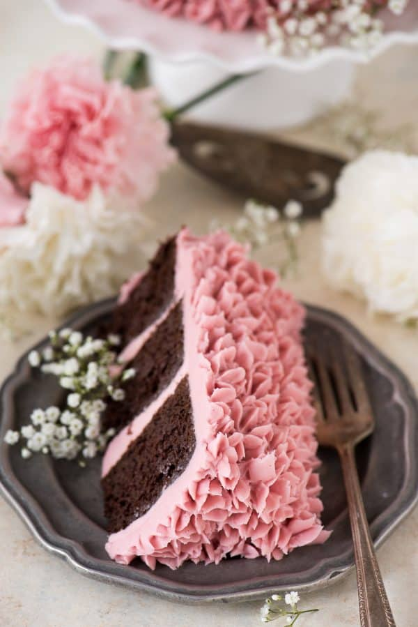 piece of raspberry chocolate cake covered with light pink raspberry frosting on metal plate