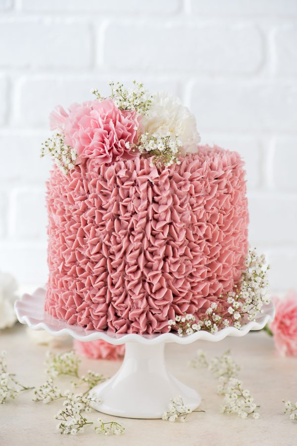 raspberry chocolate cake covered with light pink raspberry frosting and fresh flowers on a white cake plate