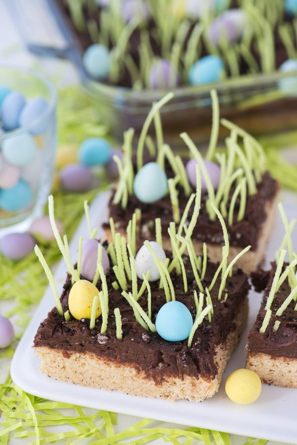 Egg Hunt Sugar Cookie Bars with edible grass cut into square on white serving tray