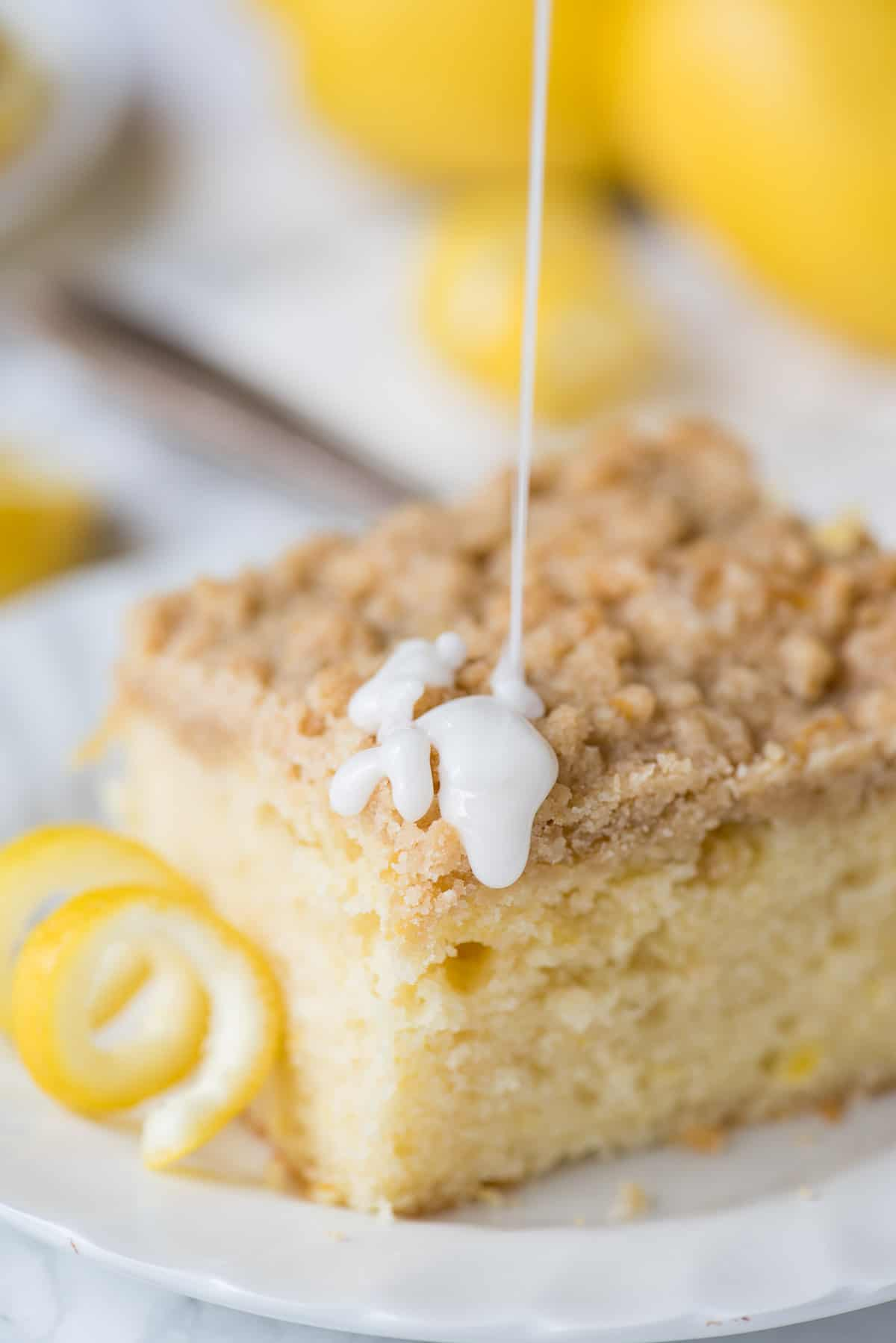 Lemon crumb cake on white plate with glaze being drizzled on top