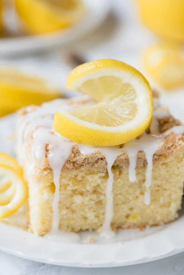Lemon crumb cake on white plate with lemon slice and glaze on top of the cake