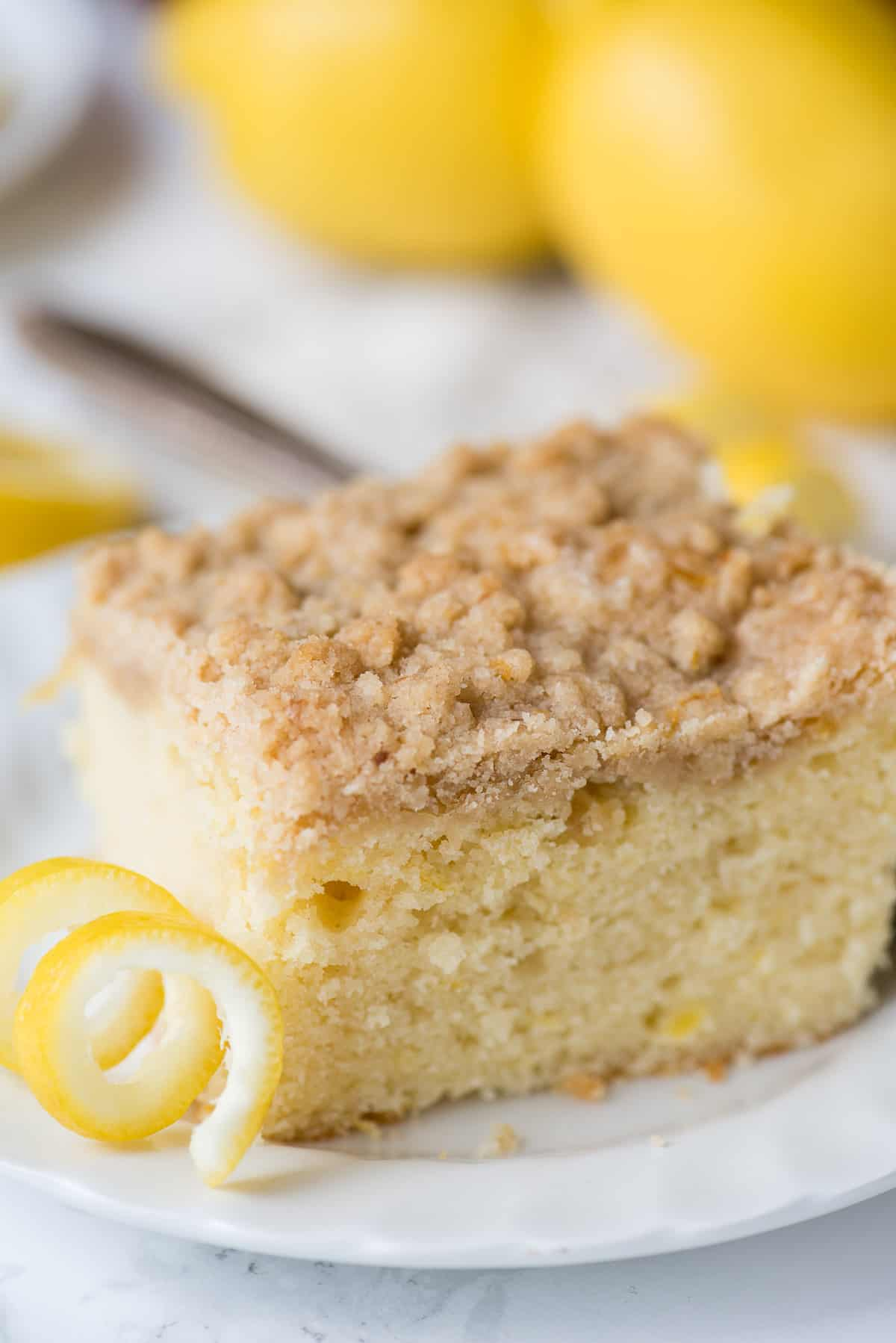 lemon crumb cake on white plate with lemons in the background