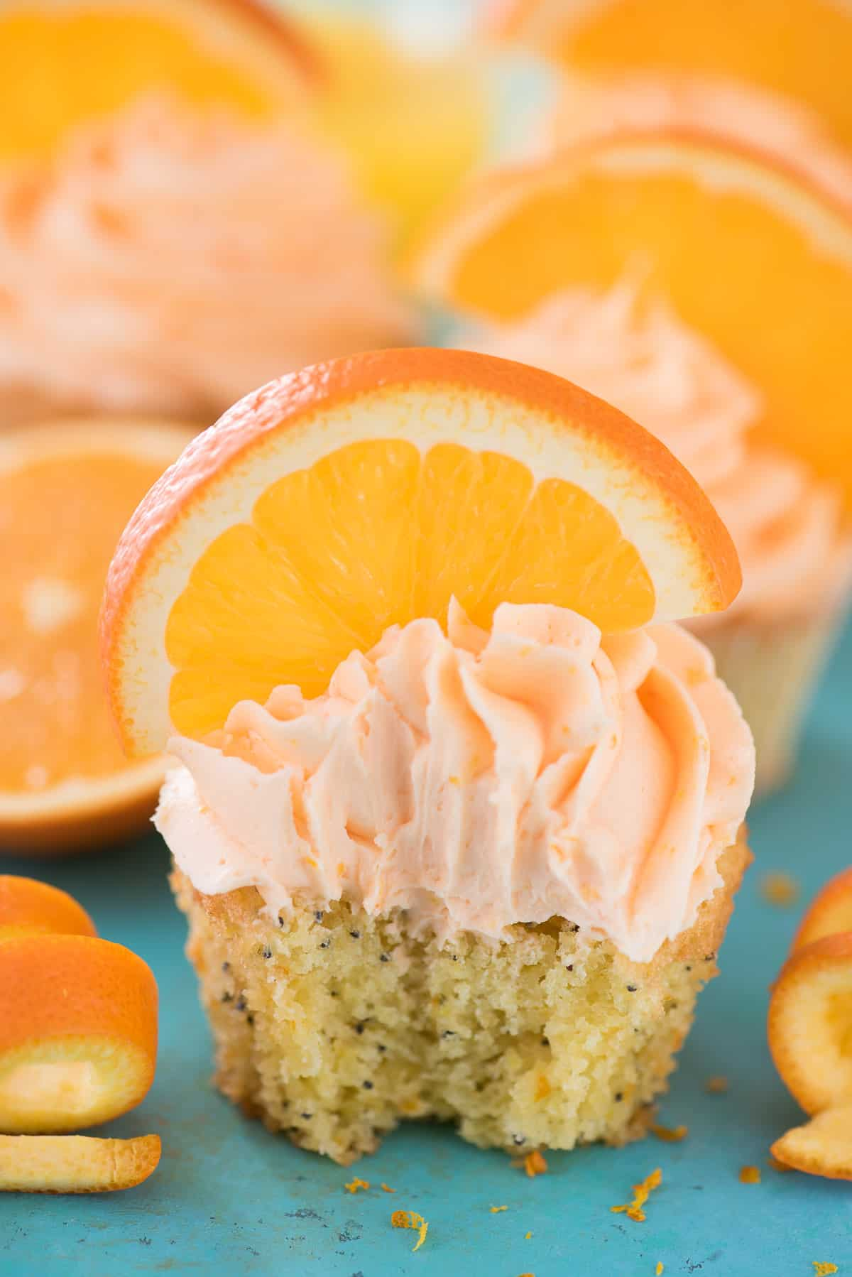 Orange Poppy Seed Cupcake with orange slice on blue background