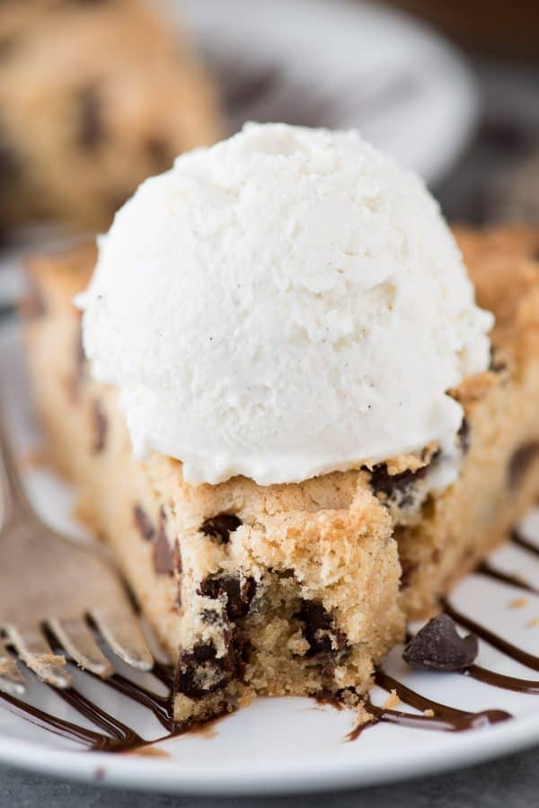 Peanut butter chocolate chip cookie pie on white plate with scoop of ice cream on top