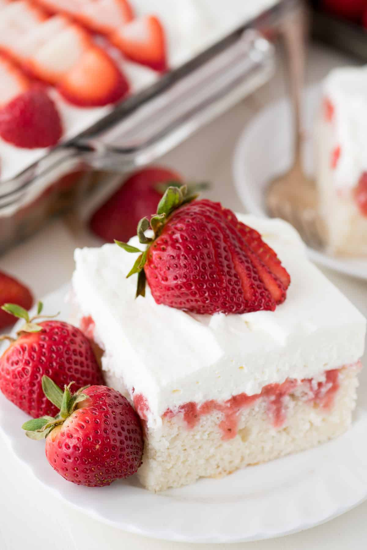 strawberry poke cake with whipped cream topping on white plate