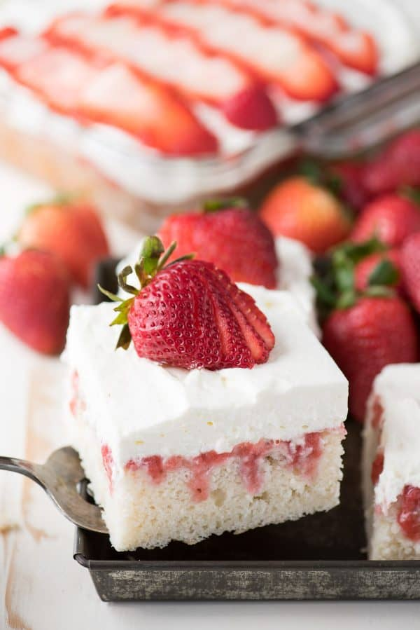 strawberry poke cake with whipped cream topping on metal serving tray