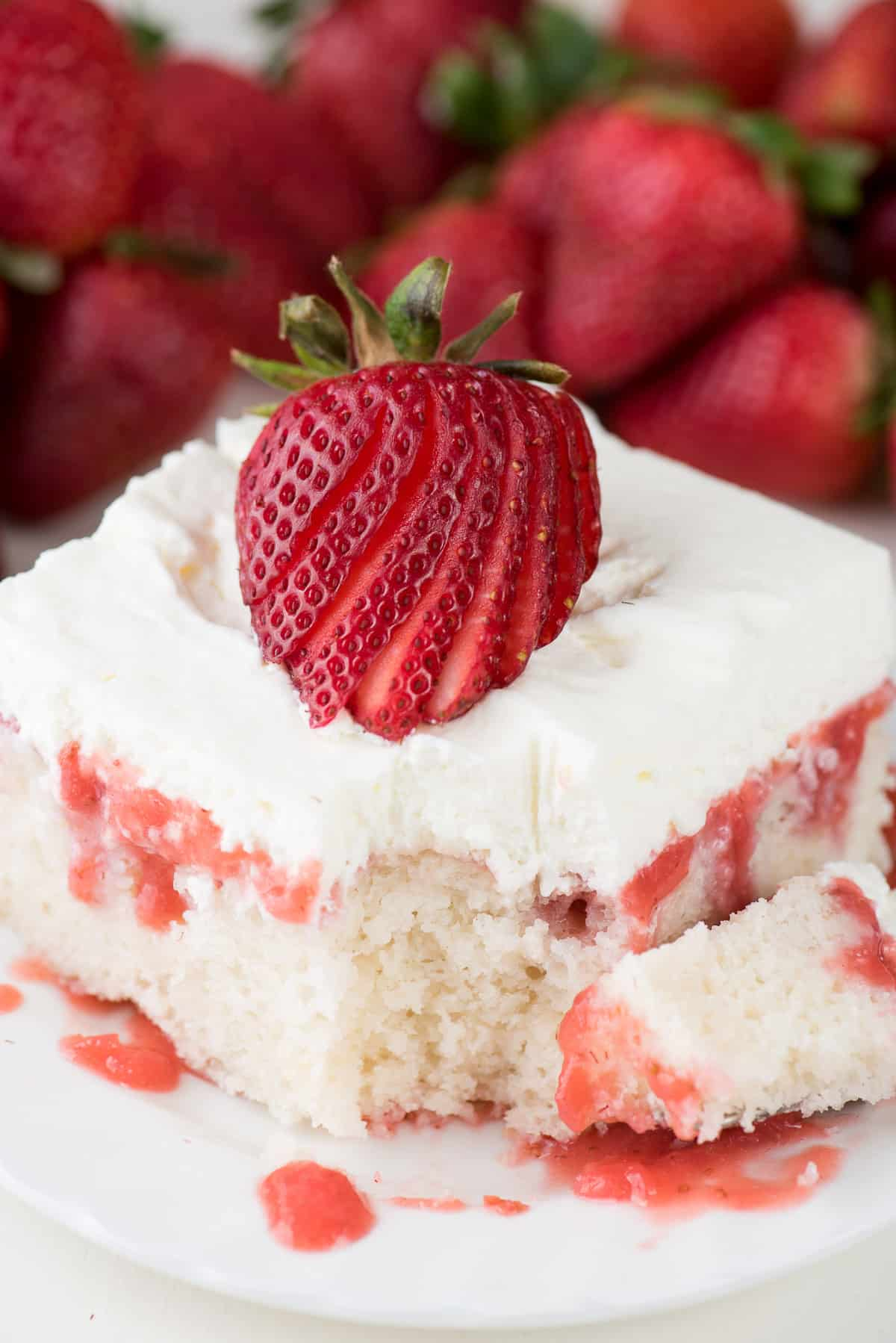 strawberry poke cake with whipped cream topping on white plate with bite taken out