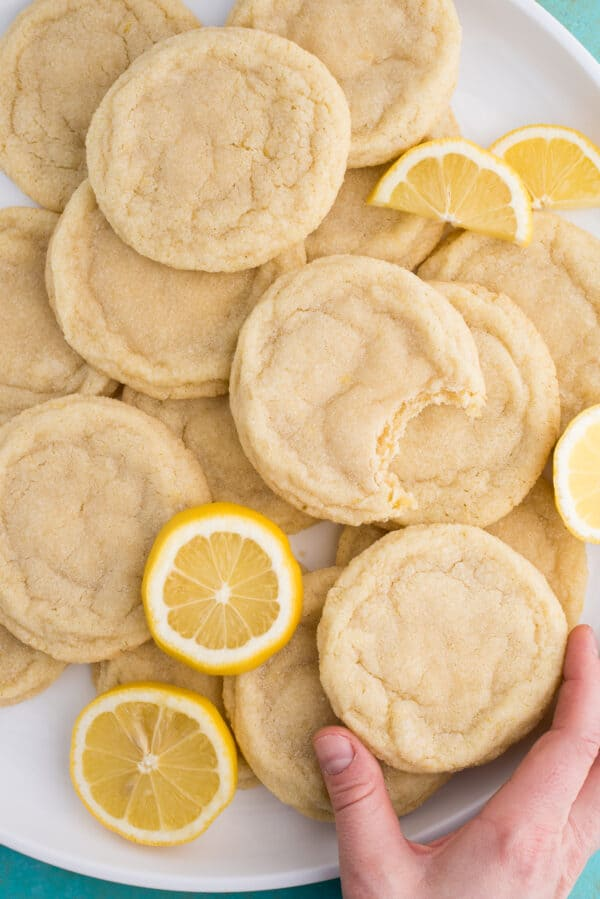 lemon sugar cookies with lemon slices on white plate on blue background