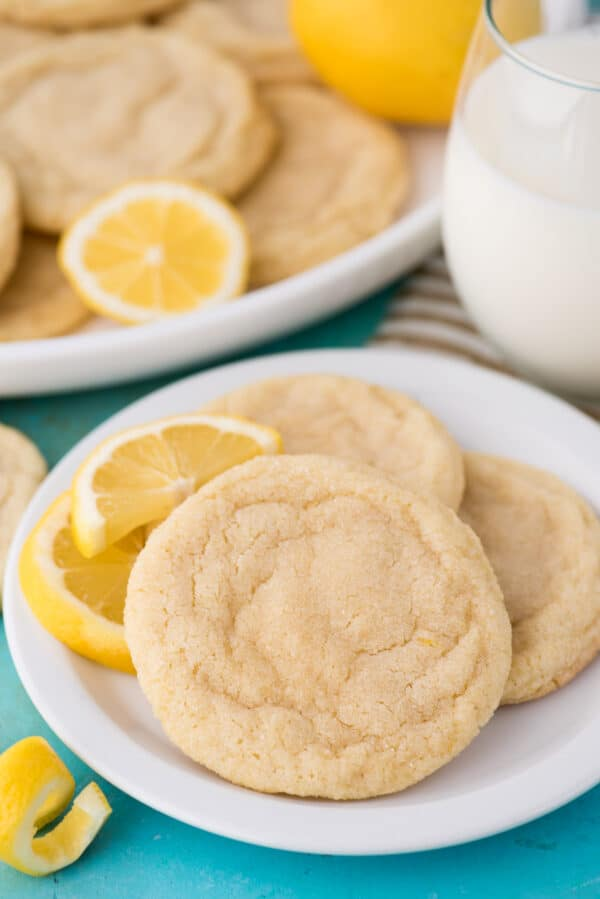 lemon cookies on white plate with glass of milk on blue background