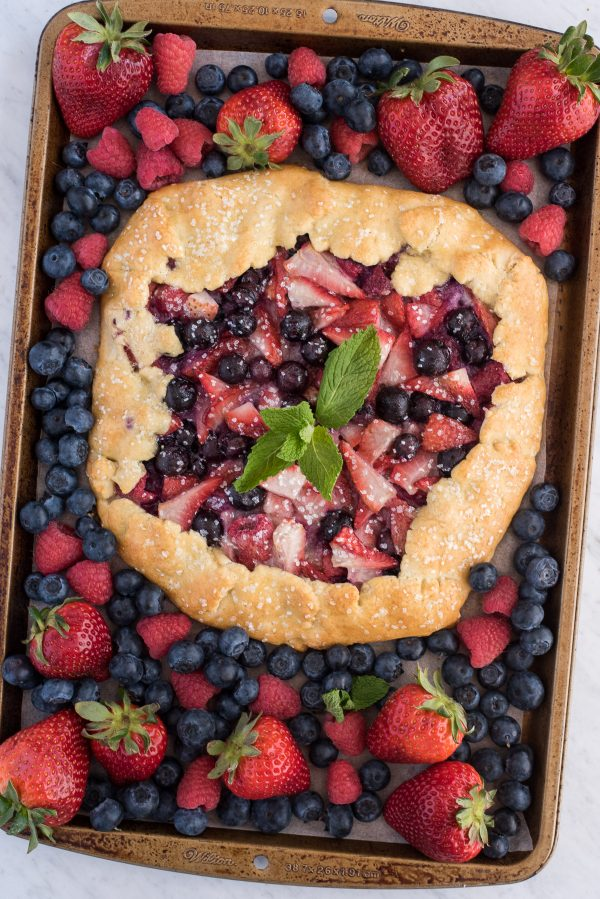 mixed berry galette with strawberries and blueberries on metal baking sheet